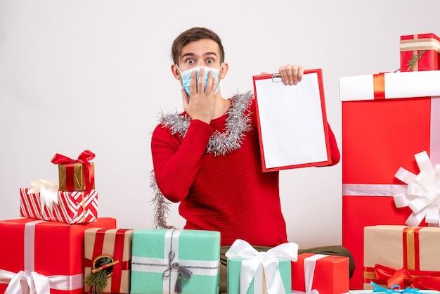 Widok z przodu młody człowiek z maską, kładąc rękę na twarzy, siedząc wokół prezentów bożonarodzeniowych