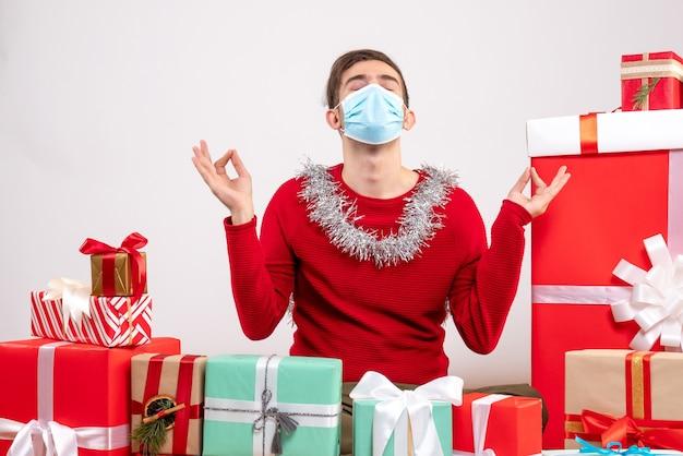 Widok z przodu młody człowiek z maską podejmowania znak medytacji siedzący wokół prezentów bożonarodzeniowych