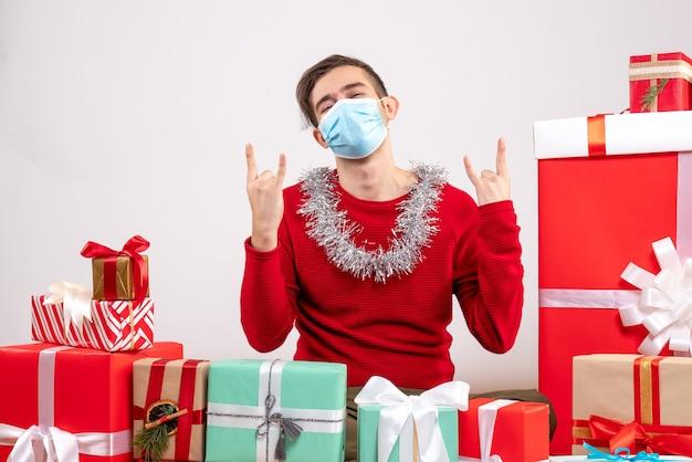 Widok z przodu młody człowiek z maską przedstawiającą znak rocka siedzi wokół prezentów bożonarodzeniowych