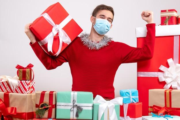 Widok z przodu młody człowiek z maską przedstawiający zwycięski gest siedzący wokół świątecznych prezentów