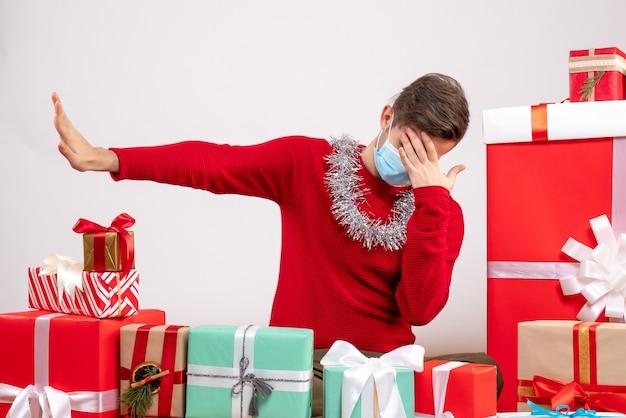 Widok z przodu młody człowiek z maską robi gest stop, siedząc wokół świątecznych prezentów