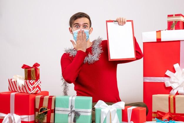 Widok z przodu młody człowiek z maską trzymając schowek siedzący wokół świątecznych prezentów