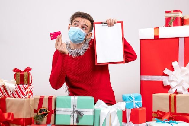 Widok z przodu młody człowiek z maską, trzymając schowka i karty, siedzący wokół świątecznych prezentów