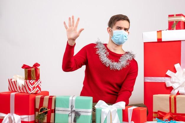 Widok z przodu młody człowiek z maską witając kogoś siedzącego wokół świątecznych prezentów