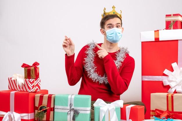 Widok z przodu młody człowiek z maską, wskazując na plecach, siedzący na podłodze prezenty świąteczne