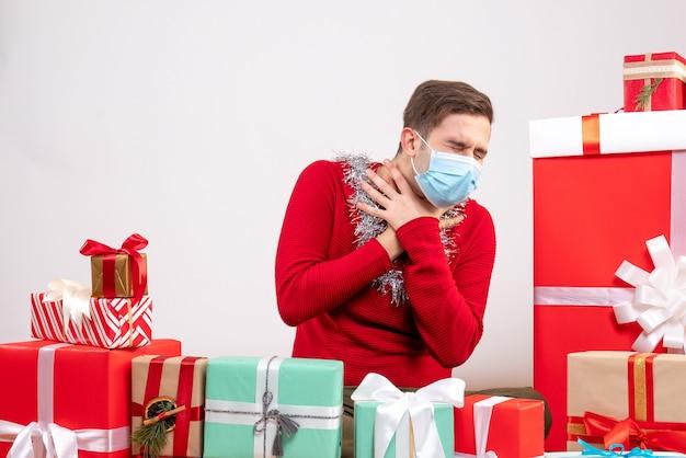 Widok z przodu młody człowiek z maską, zamykające oczy, siedzący wokół świątecznych prezentów