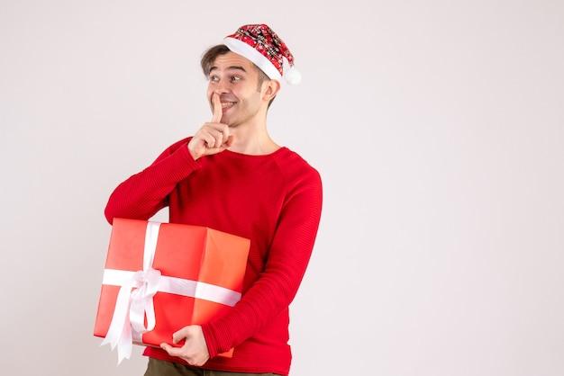 Widok z przodu młody człowiek z santa hat robi znak shh na białym tle