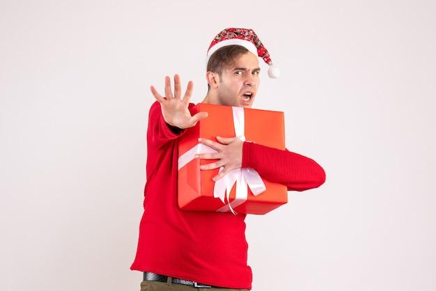 Widok z przodu młody człowiek z santa hat trzyma prezent na białym tle
