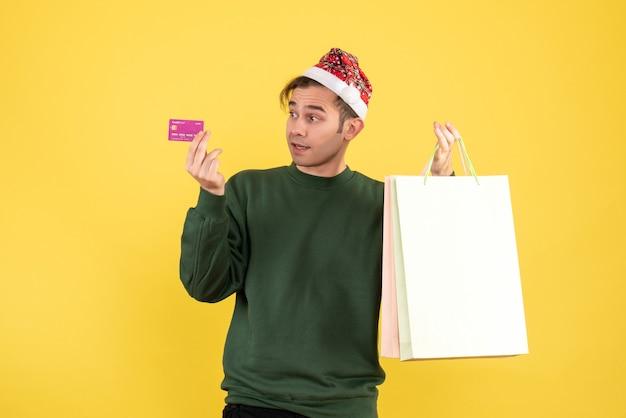Widok z przodu młody człowiek z santa hat trzymając torby na zakupy i stojącą kartę na żółtym tle miejsce kopiowania
