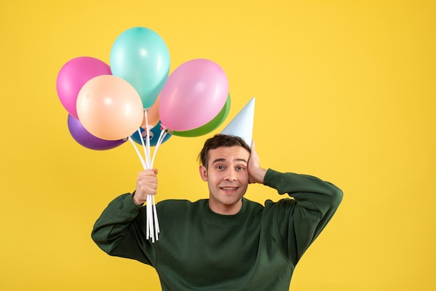 Widok z przodu młody człowiek z zielonym swetrem trzymając balony stojąc na żółto