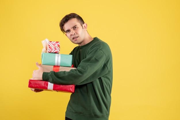 Widok z przodu młody człowiek z zielonym swetrem, ukrywając swoje dary stojąc na żółto