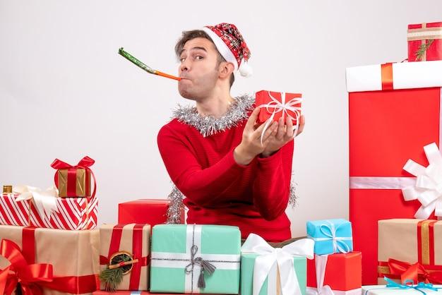 Widok z przodu młody człowiek za pomocą noisemaker siedzi wokół świątecznych prezentów
