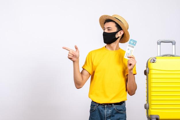 Widok z przodu młody człowiek ze słomkowym kapeluszem i maską stojący w pobliżu żółtej walizki, trzymając bilet podróżny, wskazując w lewo