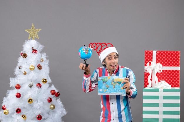 Widok z przodu młody człowiek ze spiralną wiosną santa hat trzyma mapę świata i pokazuje kulę ziemską wokół choinki i prezentów