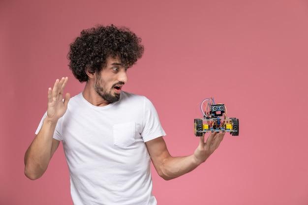 Widok z przodu młody człowiek zszokowany innowacjami robota