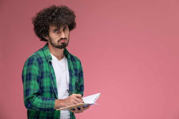 Widok z przodu młody facet robi notatki i jest sfrustrowany