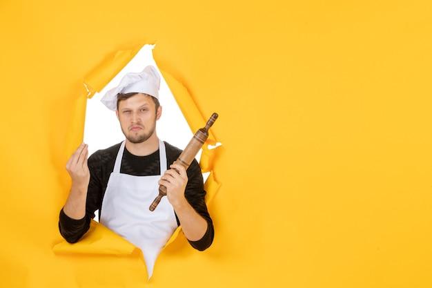 Widok z przodu młody kucharz mężczyzna w białej pelerynie trzymający wałek do ciasta na żółtym tle zdjęcie jedzenie biały człowiek kuchnia kuchnia praca kolory
