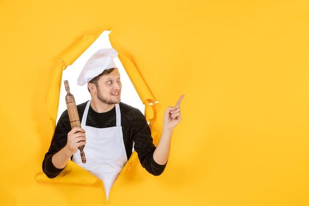 Widok z przodu młody kucharz w białej pelerynie trzymający wałek do ciasta na żółtym tle zdjęcie jedzenie biały człowiek kuchnia kuchnia praca kolor