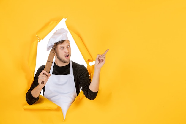 Widok z przodu młody kucharz w białej pelerynie trzymający wałek do ciasta na żółtym tle zdjęcie jedzenie człowiek kuchnia praca kolor biały