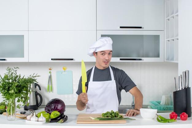 Widok z przodu młody kucharz w mundurze trzymającym nóż