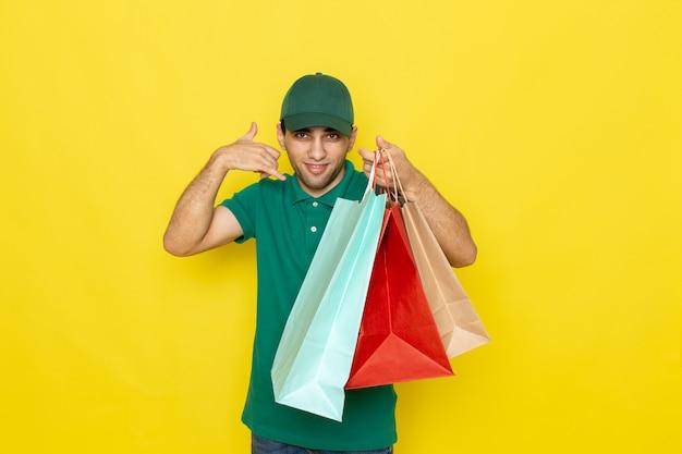 Widok z przodu młody kurier mężczyzna w zielonej koszuli zielonej czapce, trzymając paczki na zakupy i pokazujący znak wywoławczy telefonu