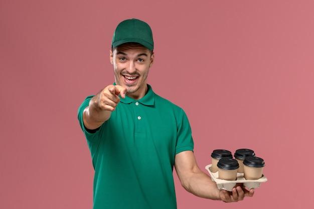 Widok z przodu młody kurier mężczyzna w zielonym mundurze, trzymając brązowe filiżanki kawy, wskazując aparat na różowym biurku