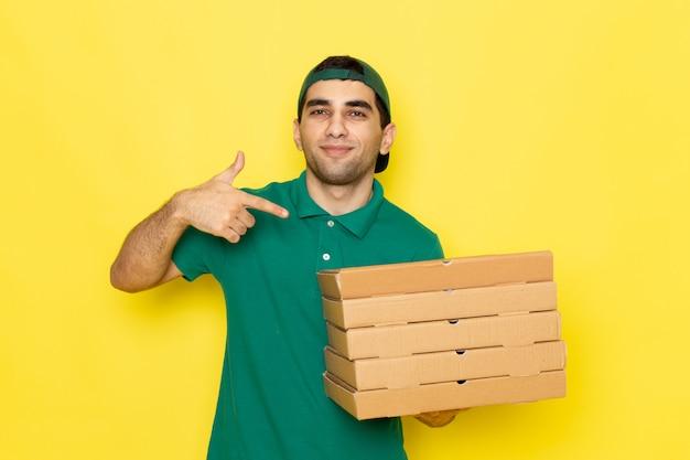 Widok z przodu młody kurier płci męskiej w zielonej koszuli, zielona czapka, uśmiechnięty i trzymając pola dostawy na żółtym tle kolor pracy dostarczania usługi