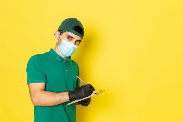 Widok z przodu młody kurier płci męskiej w zielonej koszuli, zielona czapka zapisująca notatki patrząc w kamerę na żółtym tle, świadczący usługę koloru