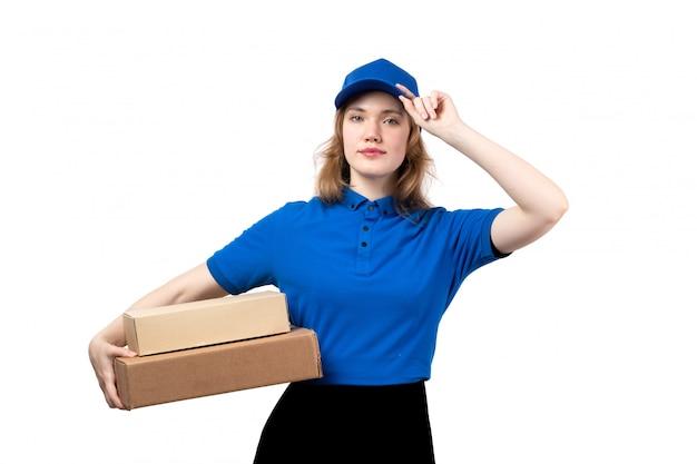 Widok z przodu młody kurier płci żeńskiej w mundurze gospodarstwa uśmiechnięte przesyłki