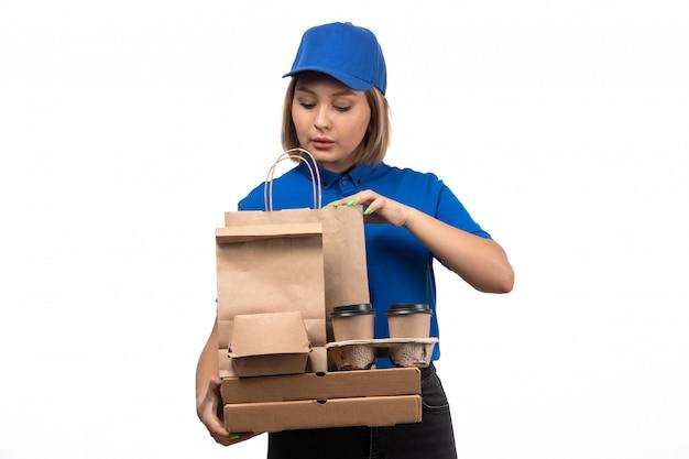 Widok z przodu młody kurier płci żeńskiej w niebieskim mundurze, trzymając opakowania dostawy żywności