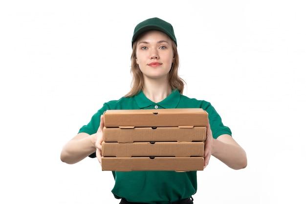 Widok z przodu młody kurier płci żeńskiej w zielonym mundurze gospodarstwa pola dostawy pizzy uśmiechnięty