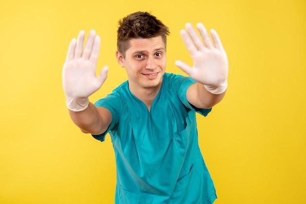 Widok z przodu młody lekarz mężczyzna w garniturze medycznym w rękawiczkach na żółtym tle