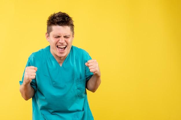 Widok z przodu młody lekarz mężczyzna w garniturze radości na żółtym tle