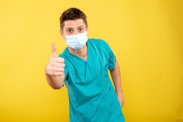 Widok z przodu młody lekarz mężczyzna w garniturze z sterylną maską na żółtym tle