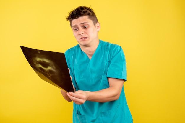 Widok z przodu młody lekarz płci męskiej w garniturze medycznym, trzymając rentgenowskie na żółtym tle