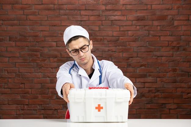Widok z przodu młody lekarz w białym garniturze medycznym z apteczką