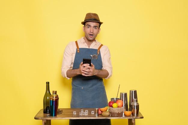 Widok z przodu młody męski barman przed stołem z shakerami i napojami trzymając telefon na żółtym tle