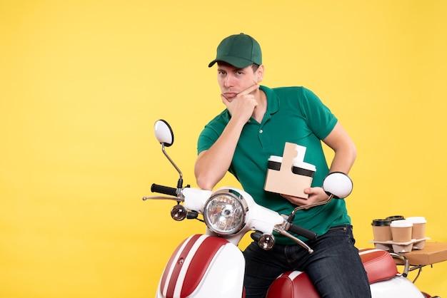 Widok z przodu młody męski kurier w zielonym mundurze z kawą na żółto