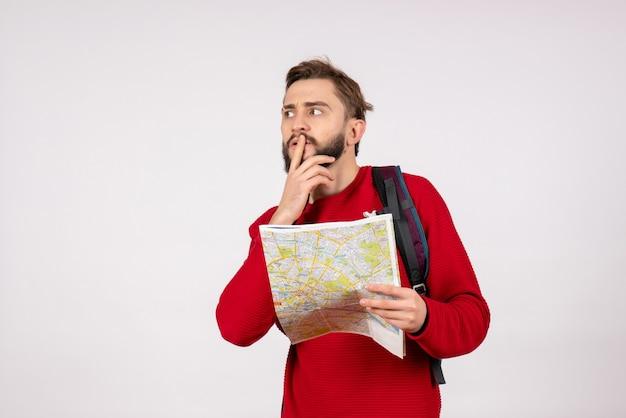 Widok z przodu młody męski turysta z plecakiem bada mapę na białej ścianie płaszczyzny miasta wakacje emocja ludzki kolor