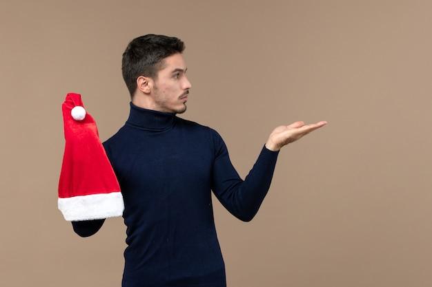 Widok z przodu młody mężczyzna bawi się z czerwoną czapką na brązowym tle boże narodzenie emocje wakacje