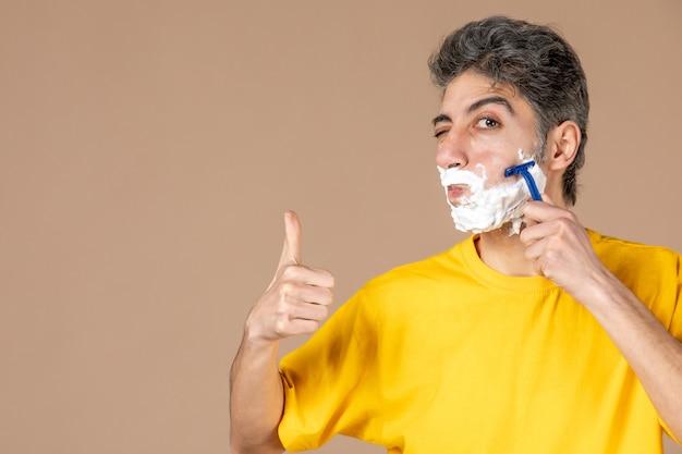 Widok z przodu młody mężczyzna do golenia jego spienionej twarzy na różowym tle