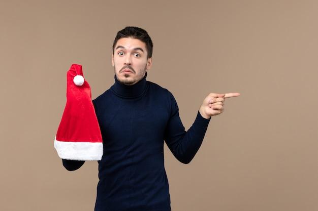 Widok z przodu młody mężczyzna gra z czerwoną czapką na brązowym tle emocji boże narodzenie nowy rok