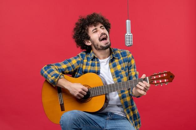 Widok z przodu młody mężczyzna grający na gitarze i śpiewający na czerwonej ścianie koncertowej muzyk koncert muzyka kolorowa na żywo