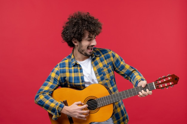 Widok z przodu młody mężczyzna grający na gitarze na czerwonej ścianie koncert na żywo gra kolorowa muzyka aplauz muzyków