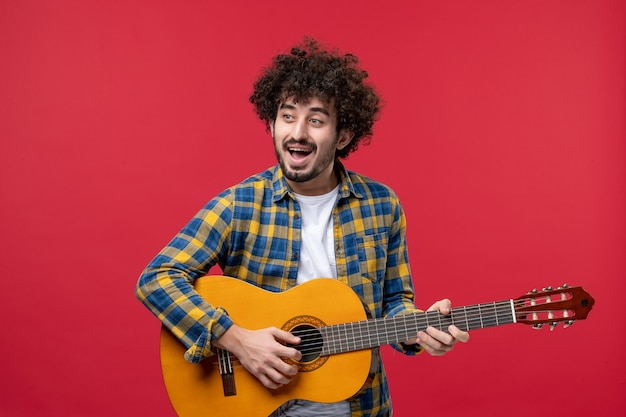 Widok z przodu młody mężczyzna grający na gitarze na czerwonej ścianie koncert na żywo kolorowa muzyka gra muzyka