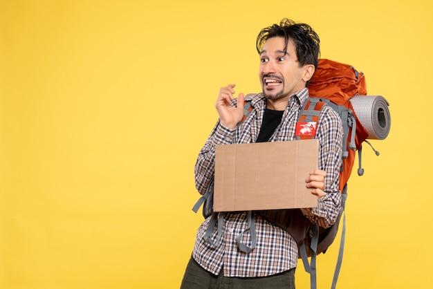 Widok z przodu młody mężczyzna idący na wędrówkę z plecakiem na żółtym tle mapa kolor natura firma wycieczka kampus powietrze las