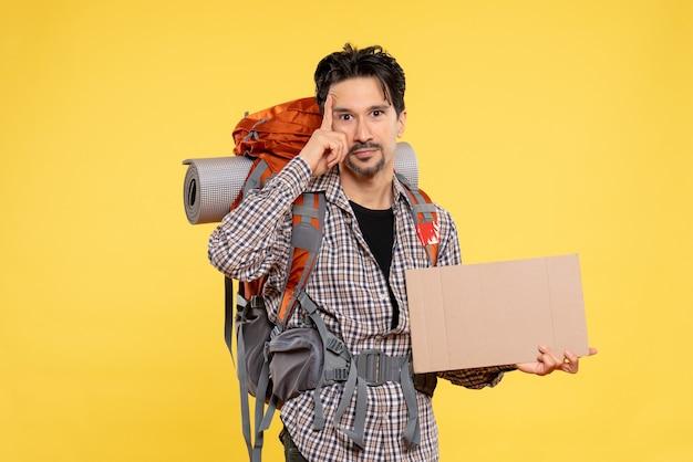 Widok z przodu młody mężczyzna idący na wędrówkę z plecakiem na żółtym tle mapa kolor powietrze natura firma wycieczka leśna kampus