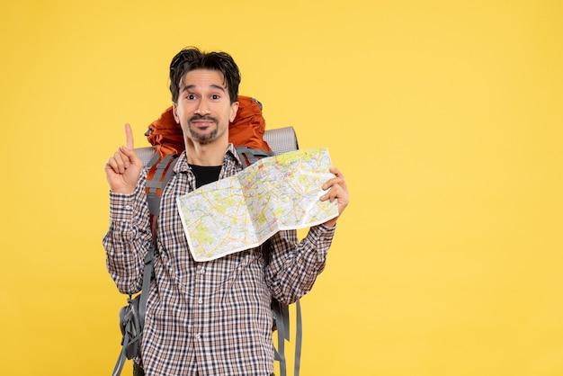 Widok z przodu młody mężczyzna idący na wędrówkę z plecakiem obserwujący mapę na żółtym tle wycieczka firmowa natura kolor kampusu