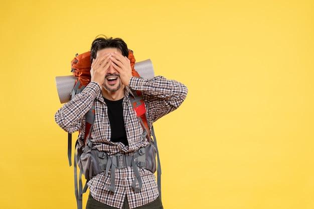 Widok z przodu młody mężczyzna idący na wędrówkę z plecakiem zakrywającym twarz na żółtym tle kolor wycieczka wysokość kampusu ludzka góra turystyczna