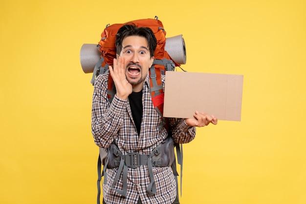 Widok z przodu młody mężczyzna idący na wędrówki z plecakiem na żółtym tle kolor podróż lotnicza natura kampus las emocja mapa